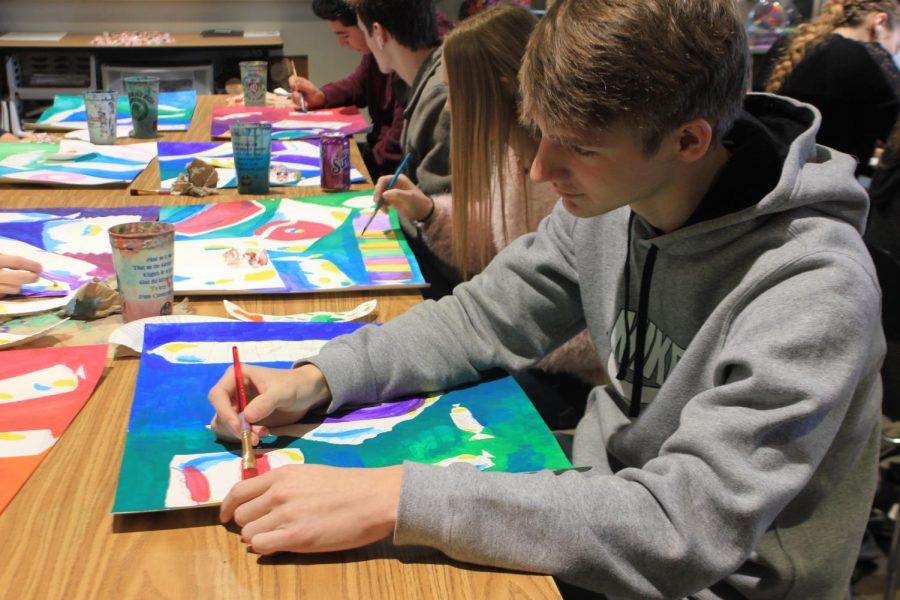 Brushstroke. Painting a red line onto his artwork, junior Schuyler Davis works on a rule of thirds candy painting. This is the first project of the semester-long class, Principles of Design.
